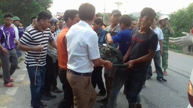 Người thân và lực lượng chức năng đưa hai anh em bị nạn ra khỏi hiện trường.