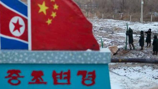 """Cảnh sát Trung Quốc xây tường rào gần cột mốc bê tông vẽ cờ Trung Quốc và Triều Tiên với dòng chữ """"Biên giới Trung Quốc - Triều Tiên"""". Ảnh: AP"""