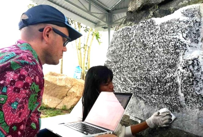 Giáo sư Arlo Griffiths nghiên cứu dòng chữ khắc trên bia đá Chăm Pa. Ảnh Nguyễn Quang Tuệ