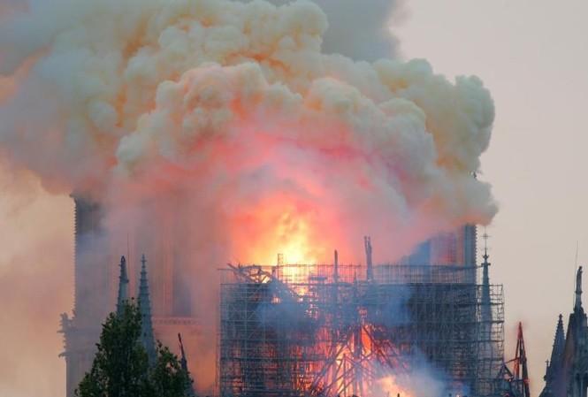 Thời khắc tháp chuông Nhà thờ Đức bà Paris đổ sập. Ảnh: Reuters