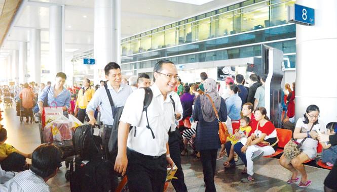 Bà con kiều bào về quê đón Tết Ất Mùi qua sân bay Tân Sơn Nhất. Ảnh: Ngô Bình.