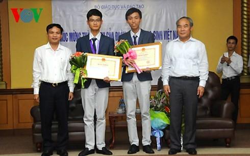 Thứ trưởng Nguyễn Vinh Hiển trao bằng khen cho 2 học sinh đạt huy chương Vàng. Ảnh VOV