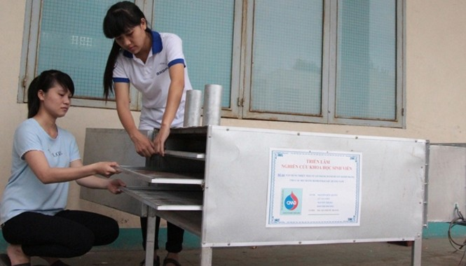 Các bạn sinh viên bên sản phẩm ứng dụng từ nhiệt thải lò bánh tráng để sấy khô bánh. Ảnh: Đào Phan.