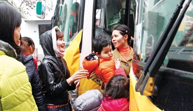 Nhiều nữ công nhân và con nhỏ hồ hởi về quê đón Tết trên những chuyến xe miễn phí. Ảnh: Xuân Tùng.
