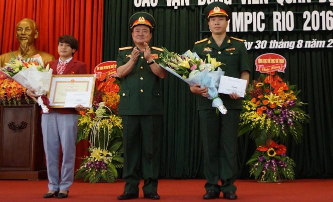 Trung tướng Trần Đơn, Thứ trưởng Bộ Quốc phòng (giữa) trao thưởng cho hai VĐV Hoàng Xuân Vinh và Văn Ngọc Tú, sáng 30/8. Ảnh: Nguyễn Minh.