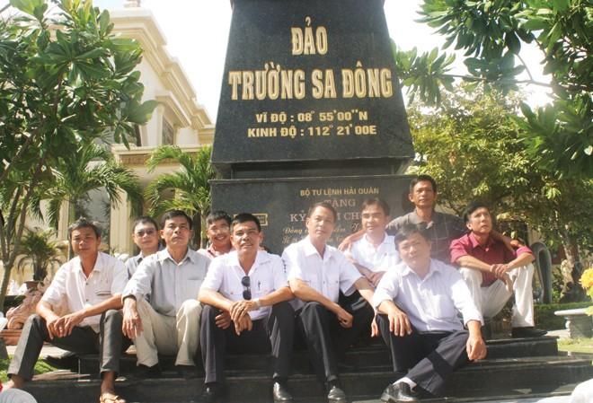 Những cựu binh Trường Sa nhiều thế hệ cùng ngồi bên mô hình cột mốc chủ quyền do anh Trần Văn Xuất làm ngay tại nhà mình. Ảnh Nguyễn Thành.
