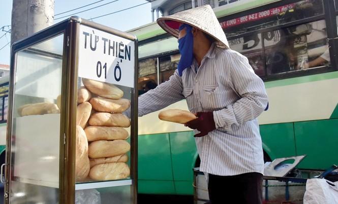 Một người mua ve chai đang lấy bánh mì từ thiện.