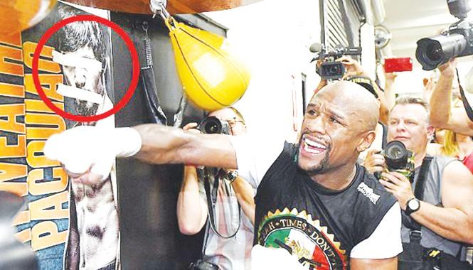 Mayweather tập luyện bên tấm poster có hình đối thủ Pacquiao của anh bị bịt mắt, bịt miệng bằng băng keo. Ảnh: Getty Images
