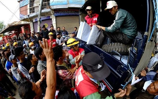 Nhân viên Hội Chữ thập Đỏ  phát lều cá nhân cho những người dân Nepal
