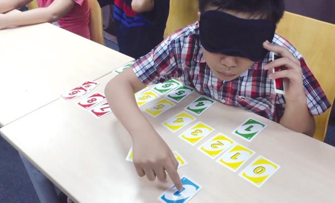 """Học viên bịt mặt xếp hình hoặc đọc chữ là một trong những hoạt động của chương trình """"kích hoạt não giữa""""."""