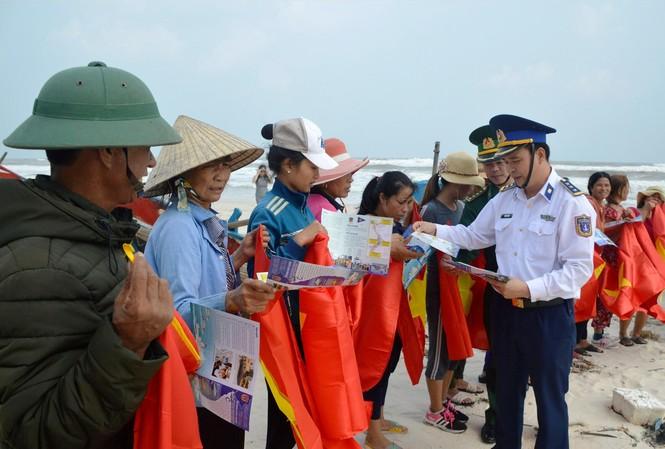 Vùng CSB 1 tặng cờ Tổ quốc và cấp phát tờ rơi tuyên truyền cho bà con ngư dân ở huyện Lệ Thủy (Quảng Bình). Ảnh: M.T