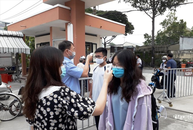 Giáo viên trường THPT chuyên Nguyễn Hữu Huân (quận Thủ Đức, TPHCM) đo thân nhiệt cho học sinh khi dịch COVID-19 tái xuất hiện trong cộng đồng. Ảnh: Huy Thịnh