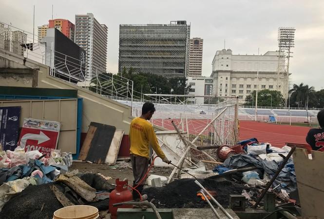Bên ngoài sân Rizal Memorial vẫn căng bạt thi công (ảnh nhỏ) trong khi bên trong vẫn ngổn ngang vật liệu  (ảnh to). Ảnh V.P