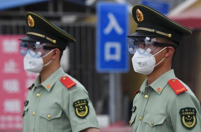 Cảnh sát bán quân sự đeo khẩu trang, kính bảo hộ khi đứng gác tại cổng chợ đầu mối Tân Phát Địa ở Bắc Kinh hôm 13/6. Ảnh: Getty Images