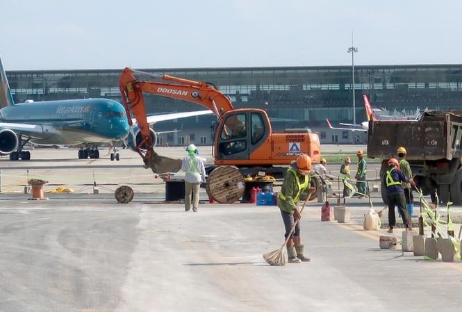 Công nhân thi công sân bay Nội Bài khi hoạt động khai thác bay vẫn diễn ra