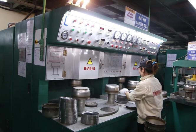Công nhân nhà máy Sunhouse ở Quốc Oai (Hà Nội) đang sản xuất lòng nồi cơm điện
