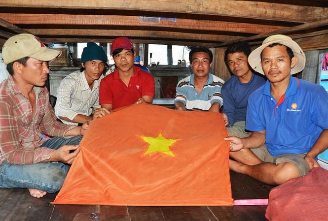 Ngư dân Nguyễn Văn Tâm (ngoài cùng bên phải) đã nhảy xuống biển vớt lá cờ Tổ quốc                      Ảnh: Văn Chương