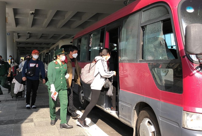 Hành khách lên xe đến địa điểm cách ly sau khi xuống sân bay Cần Thơ. Ảnh: KIM HÀ