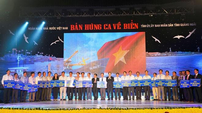 """Thống đốc Nguyễn Văn Bình trao tượng trưng trên 730 máy thông tin liên lạc cho ngư dân 28 tỉnh thành ven biển đóng tàu cá theo Nghị định 67, tối ngày 7/3 tại Chương trình """"Bản hùng ca về biển"""" tổ chức tại Quảng Ngãi"""