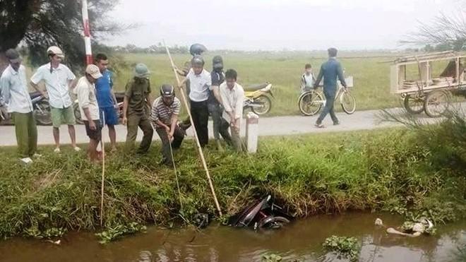 Người dân trục vớt thi thể và xe máy của nạn nhân lên bờ. Ảnh. Đ.H