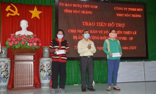 Ông Lê Văn Khannh - Giám đốc Công ty TNHH MTV XSKT Sóc Trăng trao tiền hỗ trợ cho người bán vé số