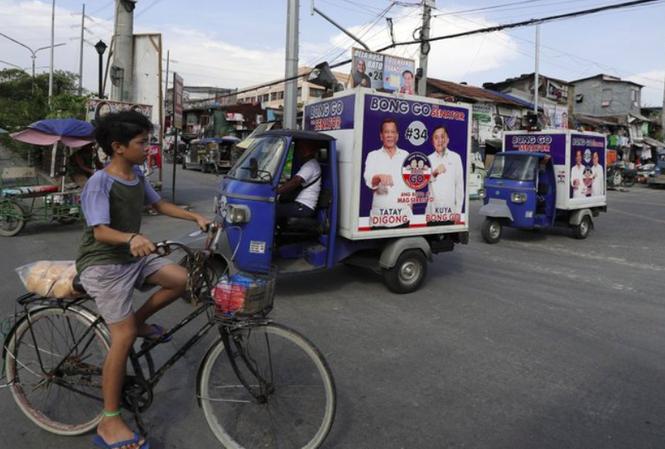Những chiếc xe dán poster vận động bầu cử chạy quanh quận Tondo hôm 9/5 ảnh: AP