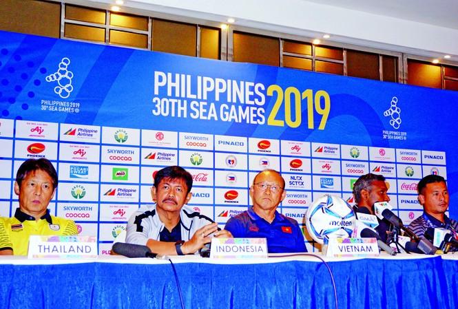 """HLV Park Hang Seo tỏ ra không hài lòng với cách điều hành cuộc họp báo trước loạt trận mở màn môn bóng đá nam SEA Games khi phải ngồi nghe HLV trưởng U22 Thái Lan """"chiếm sóng"""" ảnh: HỮU PHẠM"""