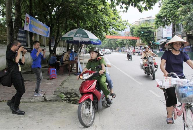 Đại úy Vũ Đức Lợi chở thí sinh Trần Thị Yến đến điểm thi, phía sau có xe chuyên dụng của CSGT hú còi hộ tống Ảnh: Trường Phong