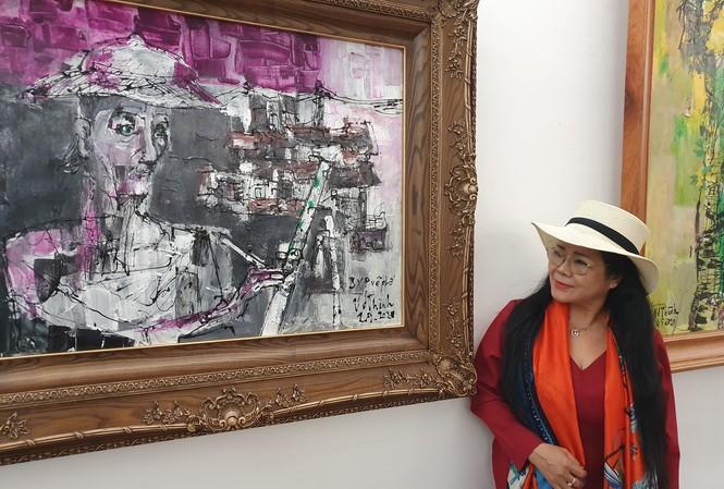 Văn Dương Thành bên bức chân dung Bùi Xuân Phái do chị vẽ.