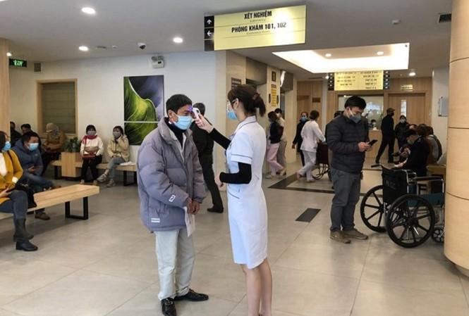 Đo thân nhiệt cho người đến khám tại Bệnh viện Ung bướu Hà Nội. Ảnh: Internet