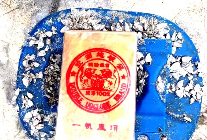 21 bánh hình chữ nhật bao gói bằng nylon có in hình dạng khuôn dấu kèm chữ Trung Quốc và ký tự Latinh chứa trong can nhựa này vừa được người dân phát hiện tại bờ biển xã Quảng Ngạn, huyện Quảng Điền, tỉnh TT-Huế