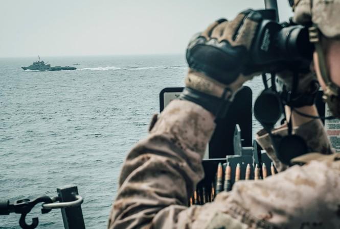 Một lính thủy đánh bộ Mỹ quan sát một tàu Iran đi qua eo biển Hormuz. Ảnh: Reuters
