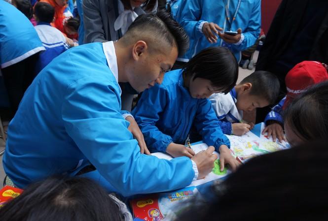 Một đại biểu thanh niên Việt Nam hướng dẫn trẻ khuyết tật tại trường Chuyên biệt Bình Minh, Đông Anh vẽ tranh. Ảnh: Thanh Huyền