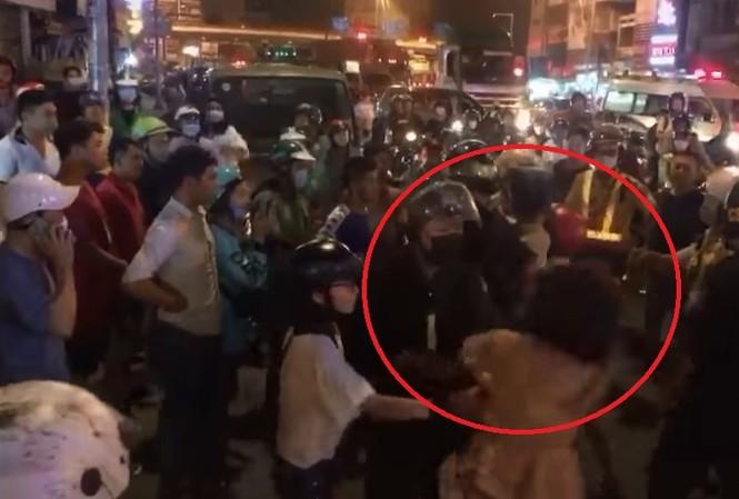 Cô gái giằng co, cắn tay Cảnh sát cơ động (ảnh cắt từ Clip).