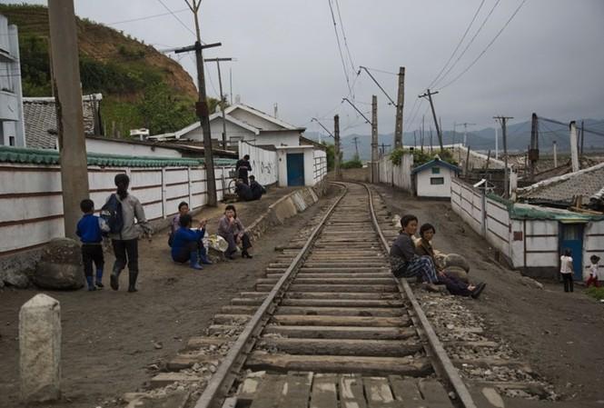 Hình ảnh người dân ngồi nghỉ bên cạnh một đường ray tàu hỏa chạy qua thị trấn nhỏ ở tỉnh Bắc Hamgyong, Triều Tiên qua góc máy phóng viên AP cho thấy cuộc sống  ở những khu vực xa xôi của Triều Tiên.