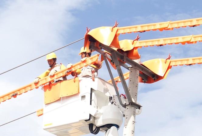 Công nhân tiến hành sửa chữa điện  trực tiếp trên đường dây mang điện. Ảnh: Thanh Trần.