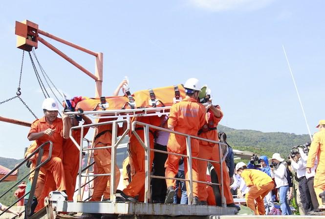 Thuyền viên tàu SAR 412 đưa một ngư dân trên biển vào bờ. Ảnh: Thanh Trần.
