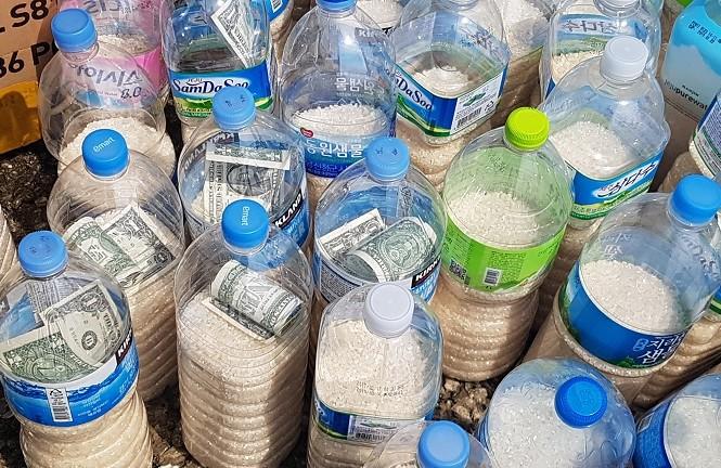 Những chai nhựa chứa gạo và một ít tiền được một số người sống tại Hàn Quốc thả trôi theo dòng biển về Triều Tiên. Ảnh: Lim Yun Suk