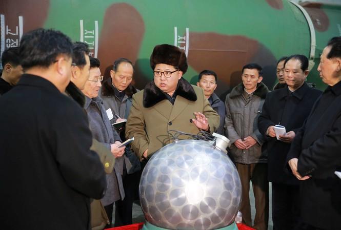 """Chủ tịch Triều Tiên Kim Jong-un (giữa) nói chuyện về các nhà khoa học và chuyên viên kĩ thuật về mô hình đầu đạn hạt nhân, được Bình Nhưỡng gọi là """"quả cầu disco"""". Ảnh: KCNA"""