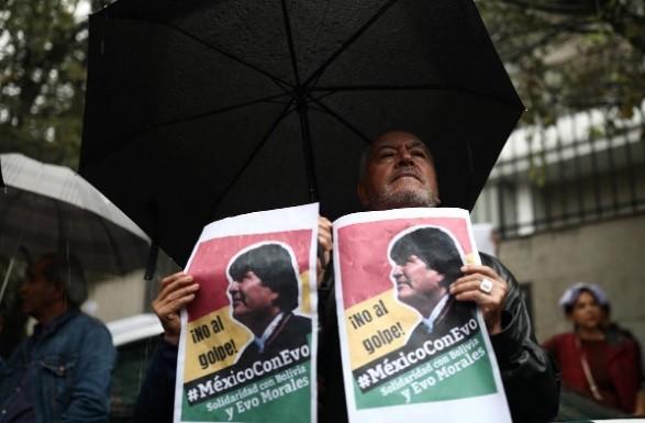 """Cuộc biểu tình ủng hộ Tổng thống Bolivia Evo Morales diễn ra bên ngoài Đại sứ quán Bolivia ở thủ đô của Mexico, ngày 11/11. Bảng hiệu có nội dung: """"Nói không với đảo chính. Mexico ủng hộ Evo. Đoàn kết với Bolivia và Evo Morales."""" Ảnh: Reuters"""