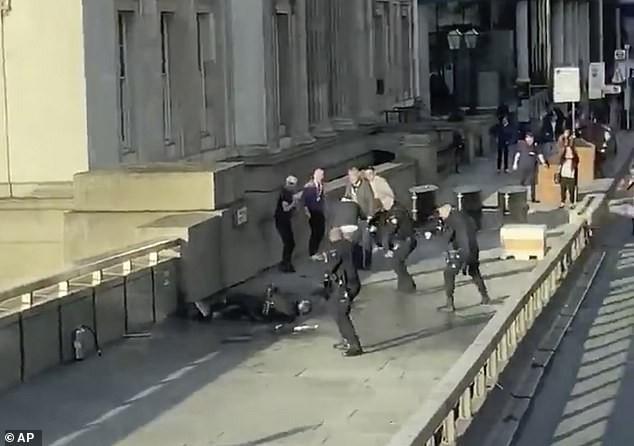 Nghi phạm (nằm dưới đất) bị cảnh sát khống chế. Ảnh: Daily Mail