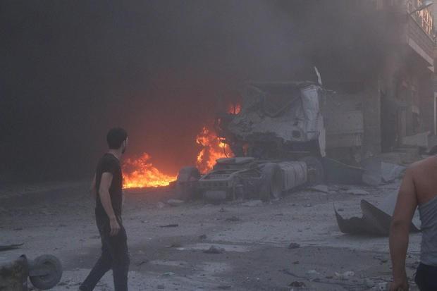 Người dân Syria đứng cạnh lửa, đống đổ nát và một xe tải hư hỏng sau một vụ không kích chết người ở tỉnh Idlib hôm 28/8.
