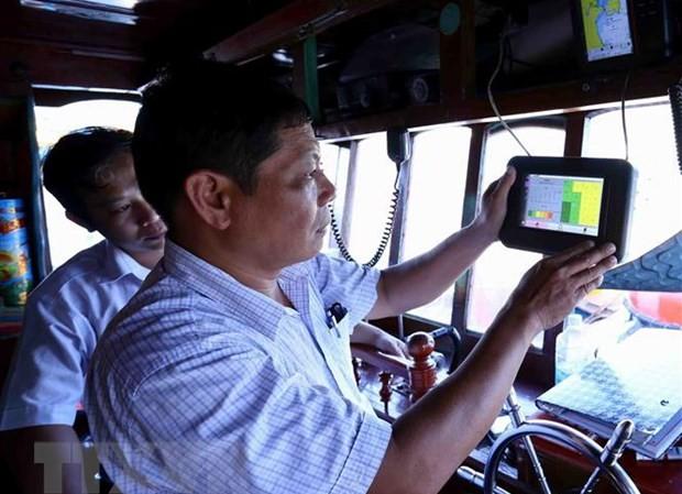 Cán bộ ngành thủy sản kiểm tra thiết bị giám sát hành trình khai thác trên tàu cá trước khi ra khơi, tại cảng cá Quy Nhơn, thành phố Quy Nhơn, tỉnh Bình Định. Ảnh: TTXVN