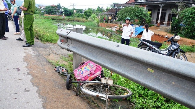 Chiếc xe đạp và hai học sinh bị ô tô hất văng xa 10 mét, va mạnh vào tường hộ lan Quốc lộ 1A.