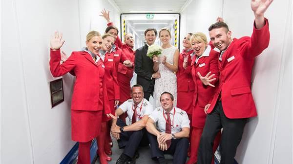 Cô dâu, chú rể tươi cười chụp ảnh cùng các tiếp viên hàng không trên máy bay