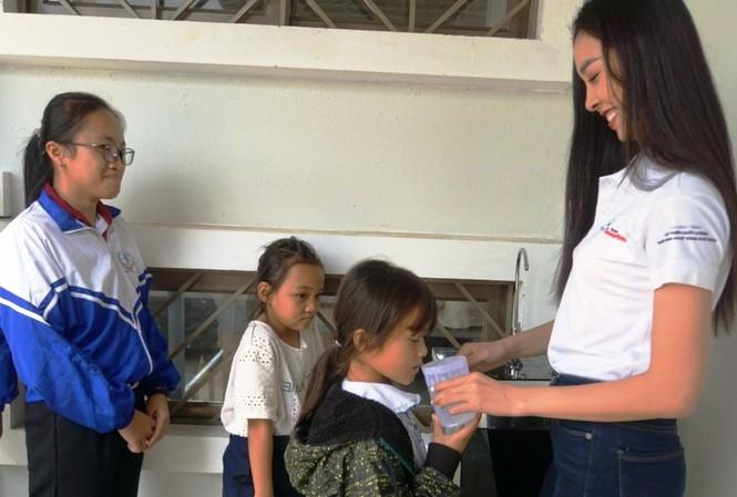 Á hậu Nguyễn Thị Thúy An rót nước cho các trẻ em uống nước tại chương trình Ký túc xá 115, tại xã Ea Dah, huyện Krông Năng, tỉnh Đắk Lắk.