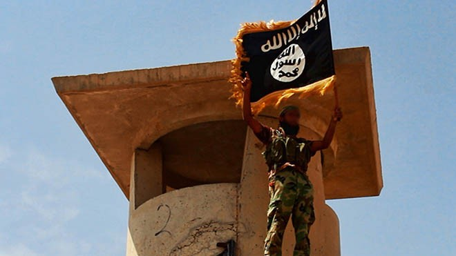 ISIS giơ cờ chiến thắng sau khi chiếm giữ một trạm kiểm soát quân sự tại miền bắc Iraq (Ảnh: RT)