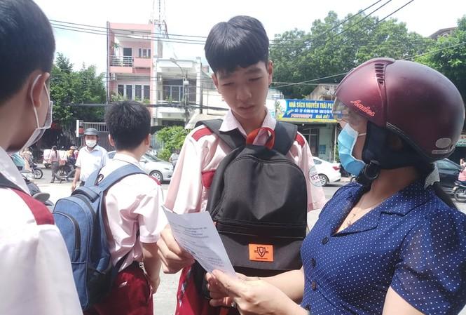 Giáo viên và thí sinh trao đổi bài thi môn Ngữ văn tại điểm thi trường THCS Nguyễn Trãi, Gò Vấp