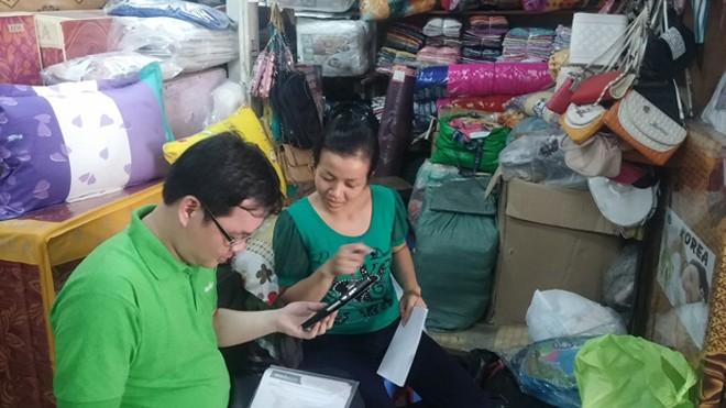Hình ảnh nhân viên MuaBanNhanh.com hướng dẫn các tiểu thương tại chợ bán hàng bằng smartphone