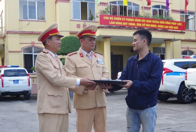 Đại diện Phòng CSGT, Công an tỉnh Hà Nam trao trả tài sản cho người đánh rơi - Ảnh: Công an Hà Nam